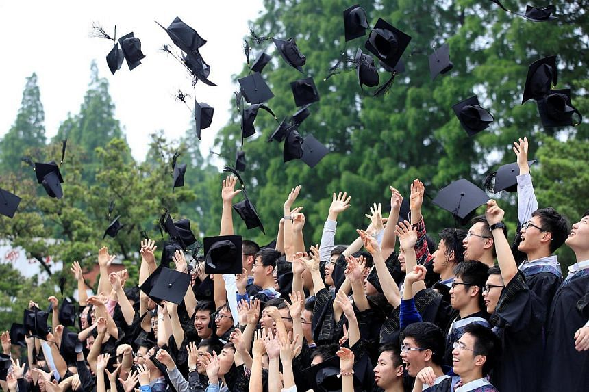 Graduates throw their mortar boards as they pose for pictures at an university in China on May 31.