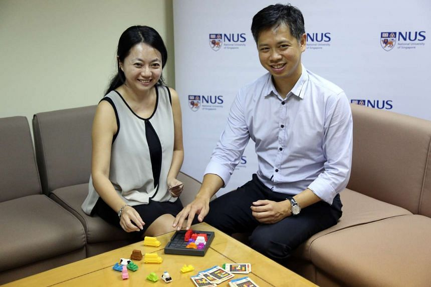 NUS researchers Assistant Professor Tsai Fen-Fang (left) and Assistant Professor Ryan Hong demonstrate the puzzle game that was used in the study to assess parental intrusiveness.