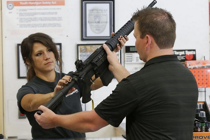 A staff member (left) showing an AR-15 semi-automatic gun to a customer at Action Target on June 17 in Springville, Utah.