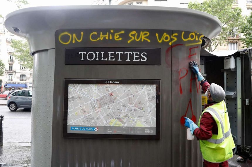 """A city employee cleans up public toilet bearing a graffiti reading """"We crap on your laws"""", following a demonstration against labour law reforms, in Paris on June 15, 2016."""