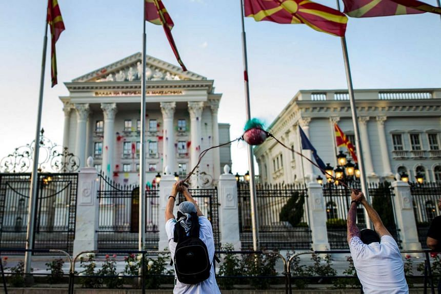 A protestor uses an improvised slingshot to throw a balloon of coloured paint on the government building during an anti-government protest in Skopje on June 15, 2016, in a series of protests dubbed Colourful Revolution.
