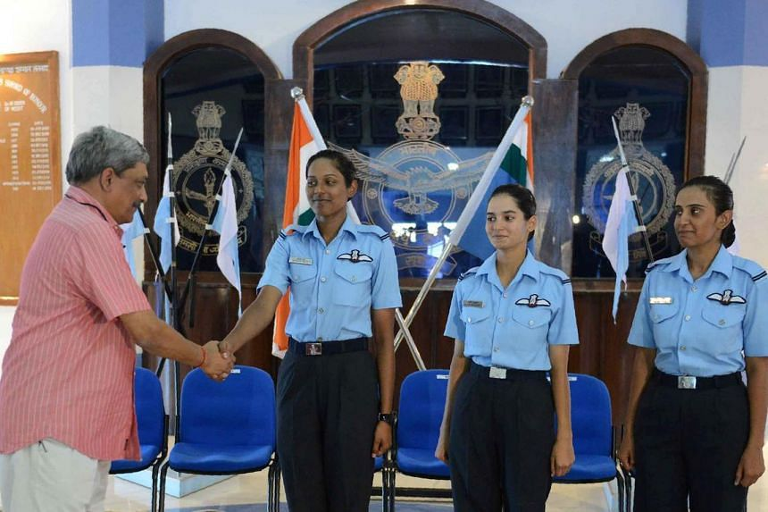 Indian Minister of Defence Manohar Parrikar (left) congratulation India's first female fighter pilots (from left) Bhawana Kanth, Avani Chaturvedi and Mohana Singh, on June 18, 2016.