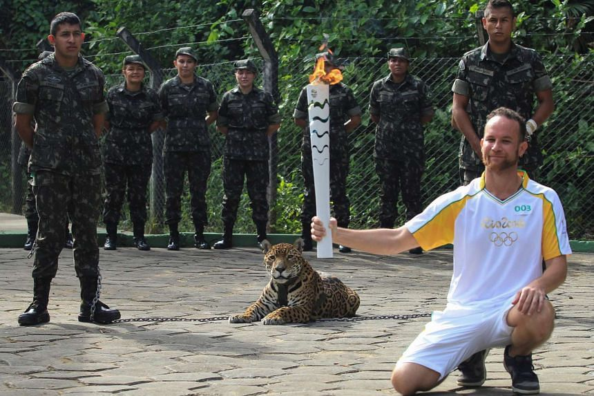 Brazilian physiotherapist Igor Simoes Andrade poses for picture next to jaguar Juma as he takes part in the Olympic Flame torch relay in Manaus, Brazil, on June 20, 2016.