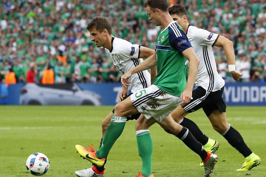 Jonny Evans (centre) of Northern Ireland in action against German players Thomas Mueller (left) and Mario Gomez (right) during the UEFA Euro 2016 group C preliminary round match between Northern Ireland and Germany at Parc des Princes in Paris, Franc