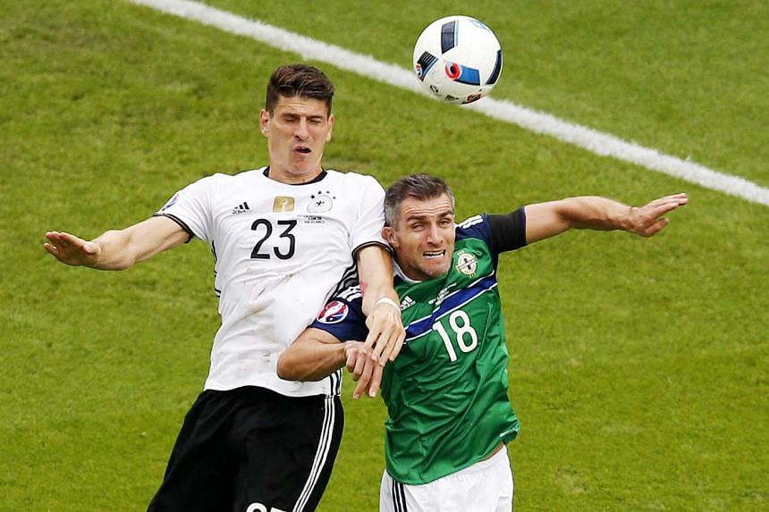 Mario Gomez (left) of Germany beats Aaron Hughes of Northern Ireland to the header during the UEFA Euro 2016 group C preliminary round match between Northern Ireland and Germany at Parc des Princes in Paris, France, on June 21, 2016.