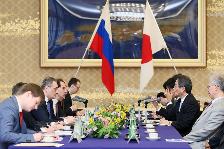 Japan's special envoy for Japan-Russia relations Chikahito Harada (second right) speaking with Russian Deputy Foreign Minister Igor Morgulov (second left) at the Iikura guest house in Tokyo on June 22, 2016.