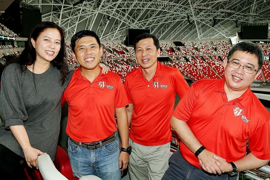 Thirty operationally ready national servicemen have volunteered to help out for this year's National Day Parade - a record number. Among them are LTC (NS) Hoe (second from left) who also roped in his wife Priscilla (extreme left); Col (NS) Lam (third