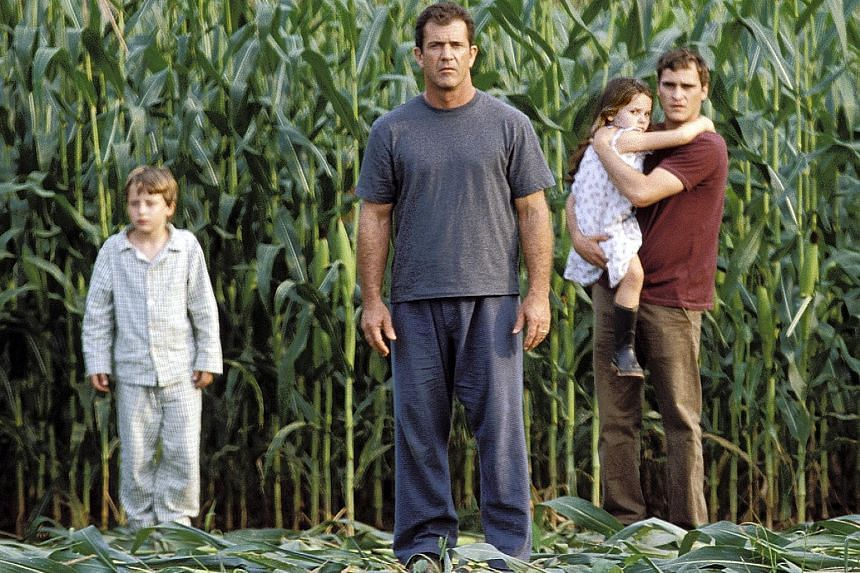 Mel Gibson (centre) as a farmer who finds crop circles in Signs.