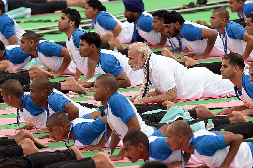 Mr Modi (in all-white top) taking part in an early morning mass yoga session along with schoolchildren, residents and government employees in the northern city of Chandigarh yesterday. He called for a focus on mitigating diabetes through yoga.