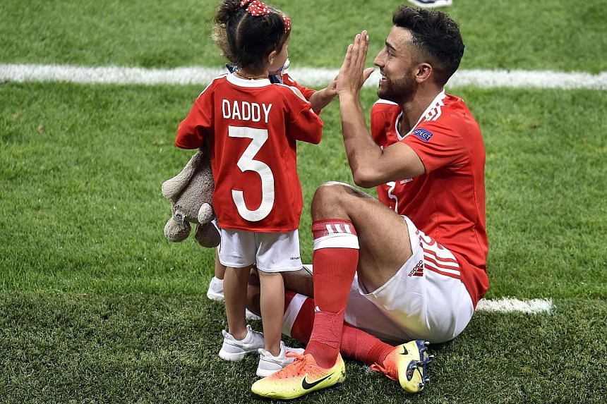 Wales defender Neil Taylor celebrates his side's 3-0 Group B win over Russia with his children. He scored the second goal of the match as Wales trounced a poor Russian side and finished as Group B winners.
