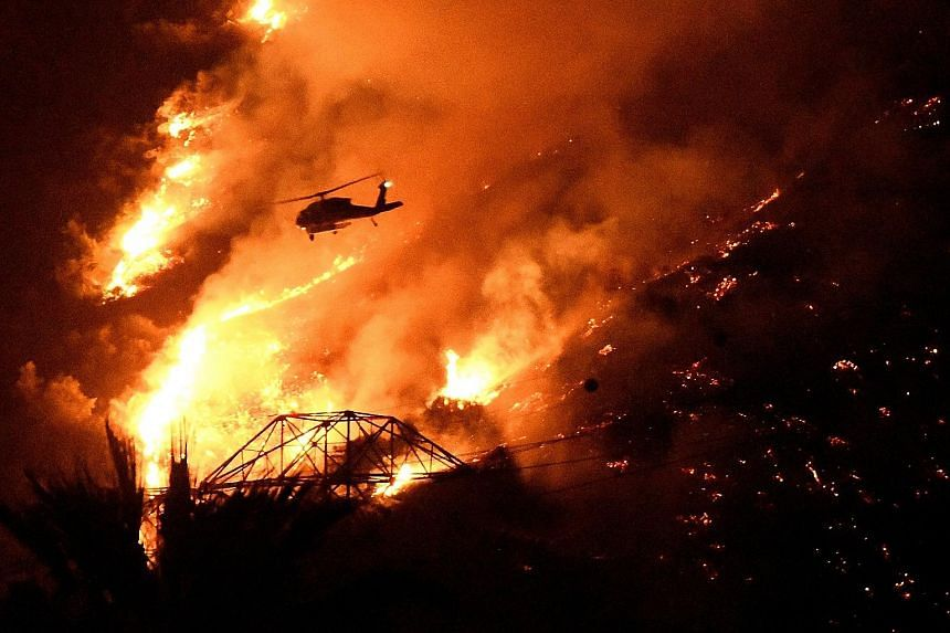Below: A fire helicopter making a night drop while battling a blaze above Azusa, California, on Monday.