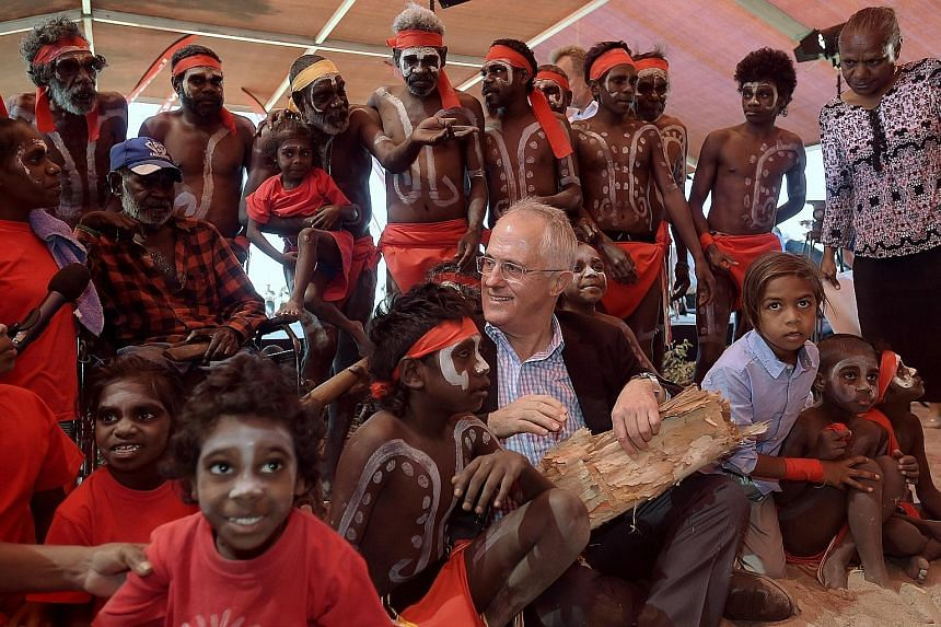 Australian Prime Minister Malcolm Turnbull with Aboriginal dancers at the Kenbi Native land claim ceremony near Darwin, Australia, yesterday. The Kenbi claim, which covers most of Cox Peninsula, was the longest-running Aboriginal land claim case in A
