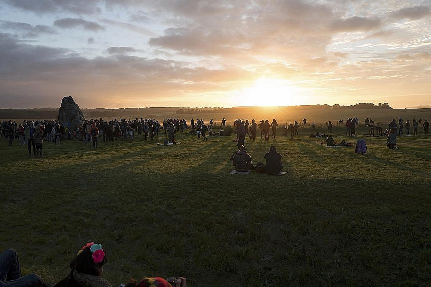 Thousands of people watching the sunrise at Stonehenge in Britain yesterday. They were at the ancient monument site to mark the summer solstice. English Heritage, which seeks to protect historical sites, said about 12,000 watched the sunrise.