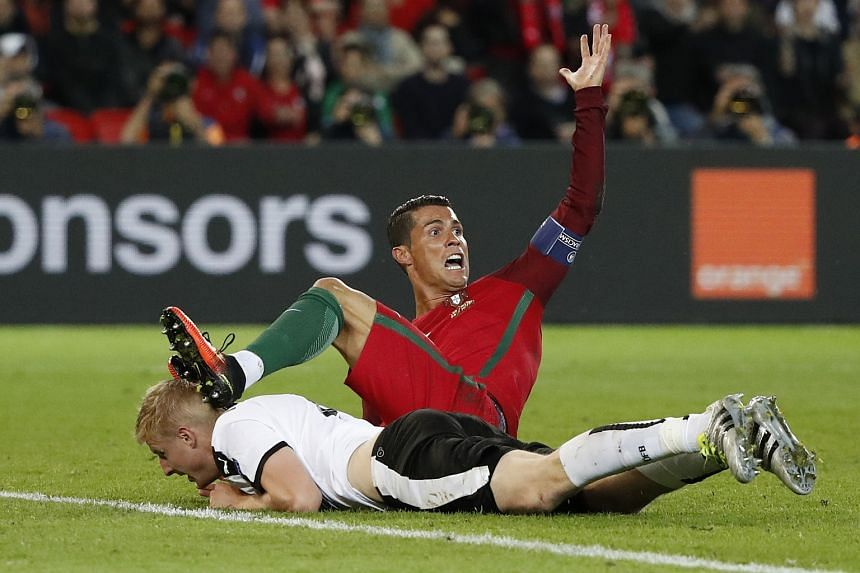 Portugal's Cristiano Ronaldo is fouled by Austria's Martin Hinteregger during their Uefa Euro group F football match.