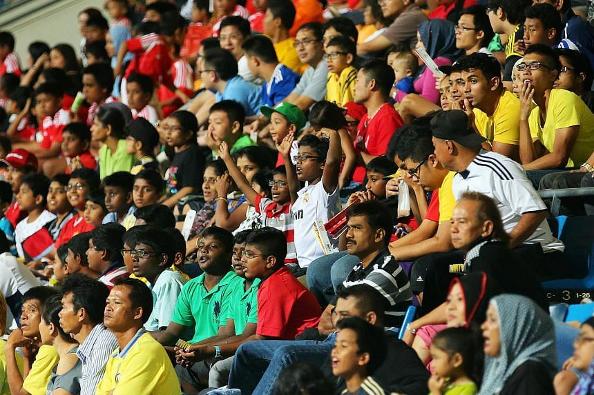 Football fans cheering at the Jalan Besar Stadium.