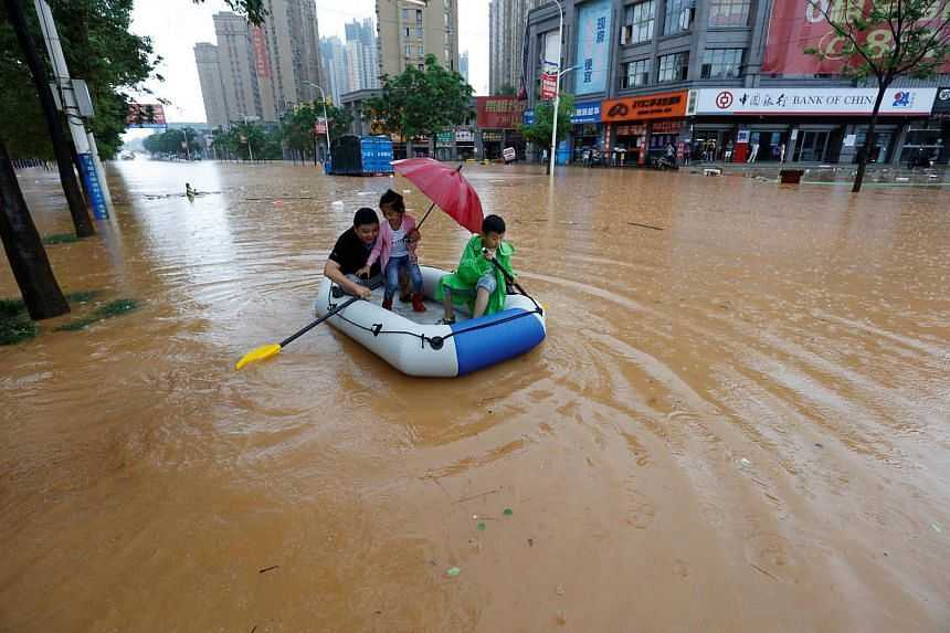 Residents make their way through a flooded area in Jiujiang, China, with an inflatable boat.