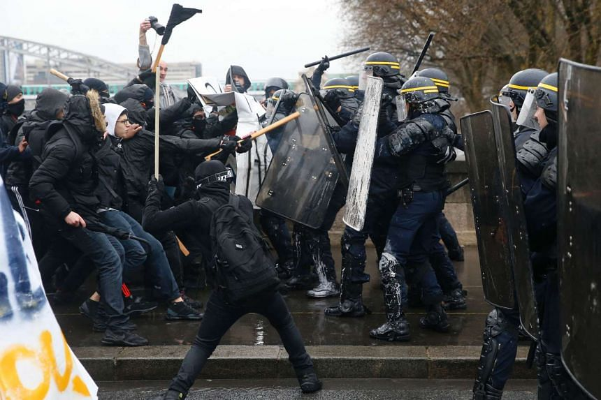 French riot police clashing with union members and students demonstrating against labour law reforms, in Paris on March 31, 2016.