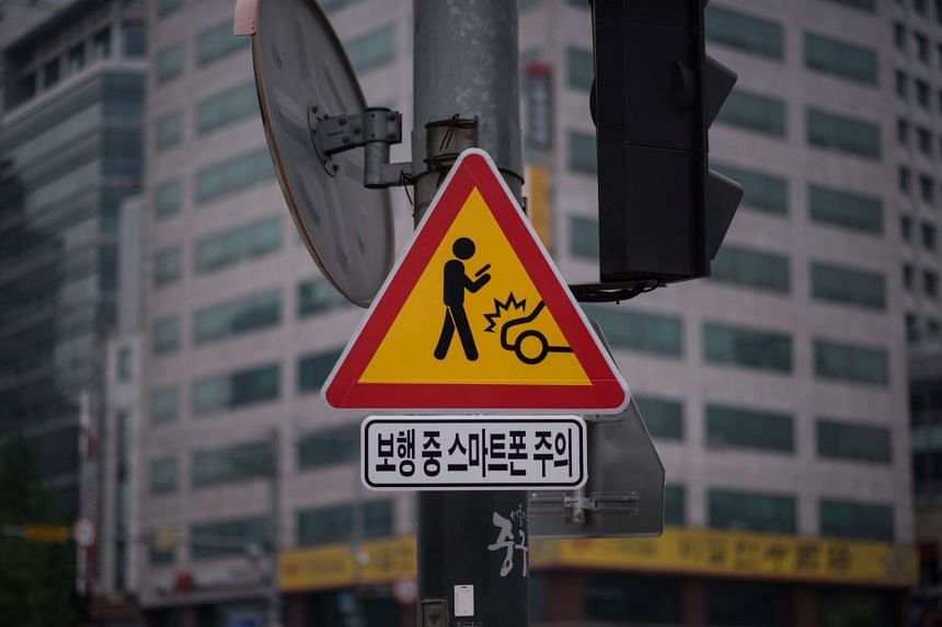 A sign warning pedestrians of the dangers of using smartphones while walking is seen in central Seoul on June 22, 2016.