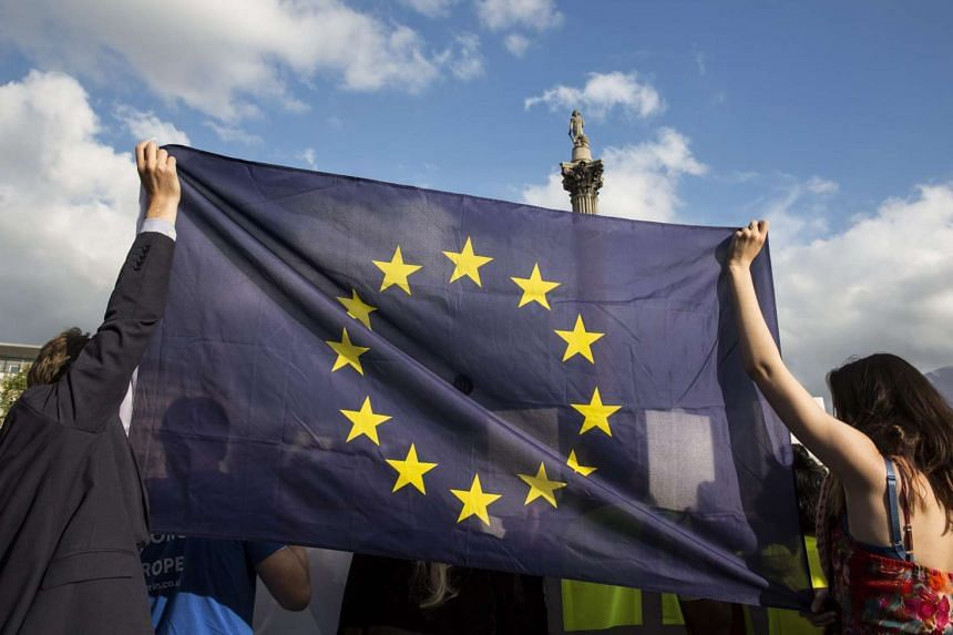 "Britons hold up an EU flag in Trafalgar Square in London during ""Remain In"" rally on June 21, 2016."