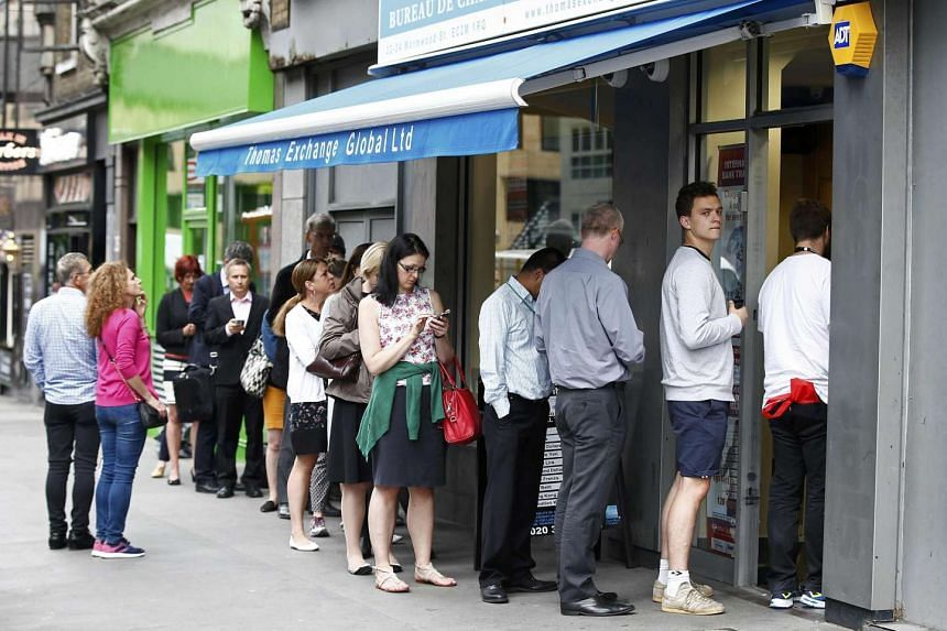 People queue for foreign exchange at a foreign exchange bureau in London, Britain on June 22, 2016.
