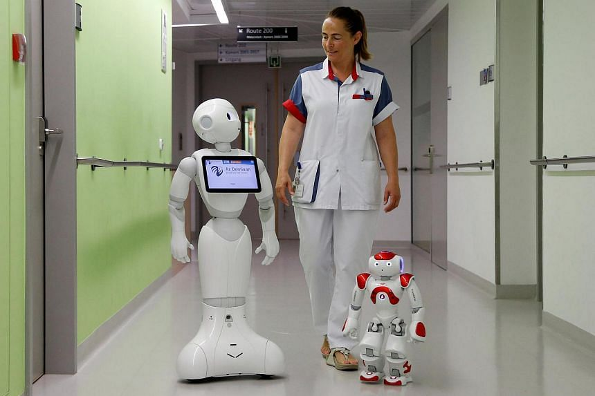 """A nurse walking with """"Pepper"""" (left) and """"Zora"""", humanoid robots designed to welcome and take care of visitors and patients, at AZ Damiaan hospital in Ostend, Belgium, on June 16."""