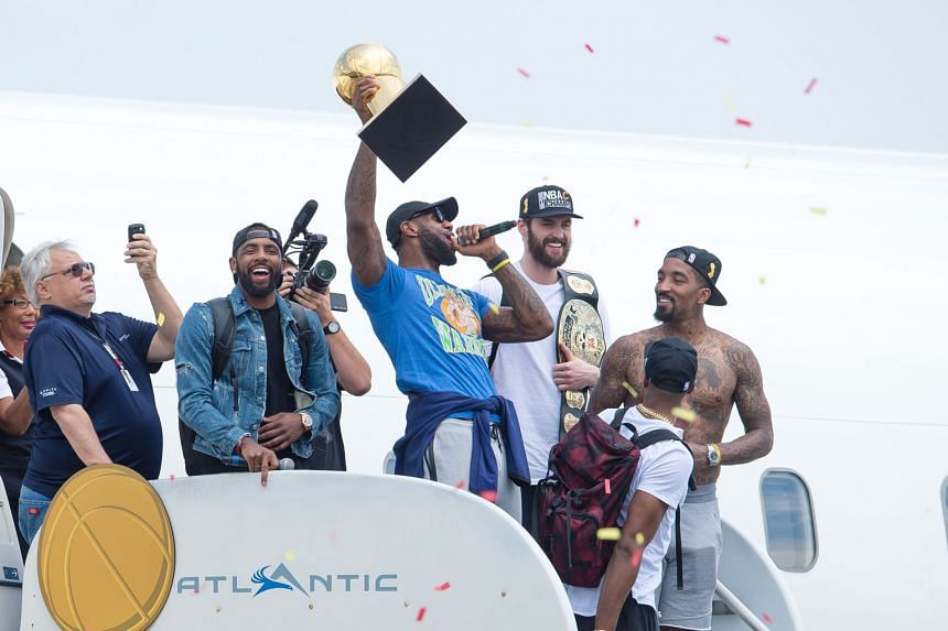"""LeBron James (holding trophy) taking a gentle jibe at their' defeated Finals opponents Golden State Warriors, as he emerged from the team plane sporting an """"Ultimate Warrior"""" T-shirt."""