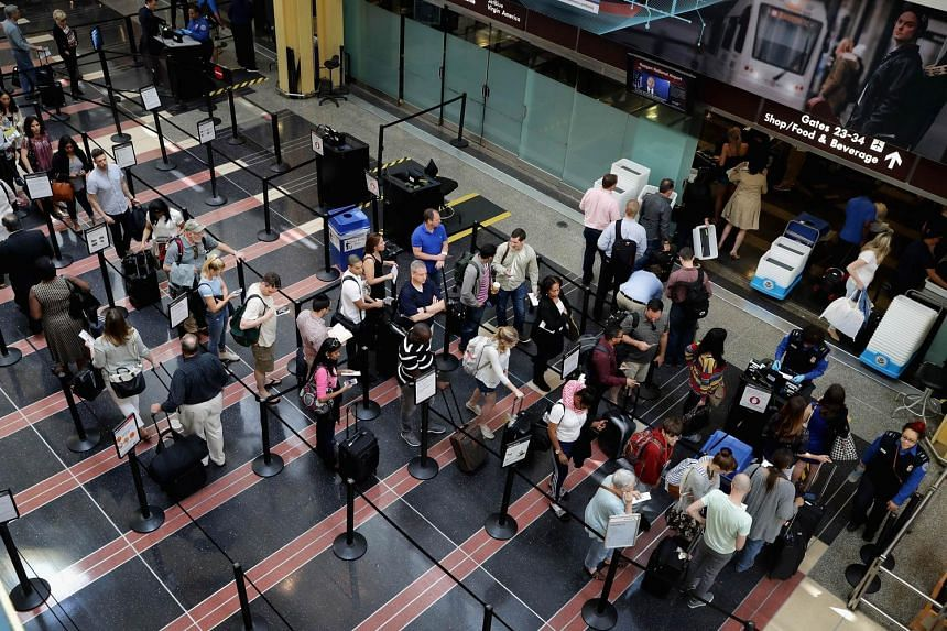 Passengers queue up outside a Transportation Security Administration checkpoint at Ronald Reagan National Airport in Arlington, on May 27, 2016.