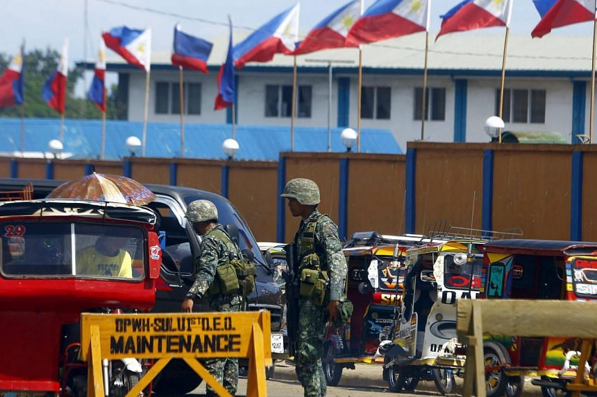 Soldiers standing guard at a military checkpoint in Sulu, southern Philippines, on June 15.