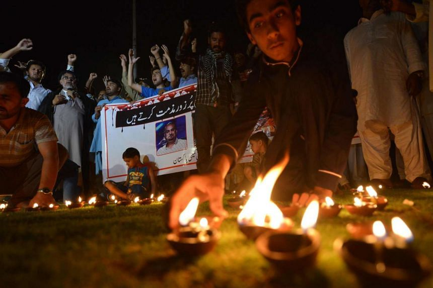 Pakistani Shi'ite Muslim protesters light oil lamps to pay tribute to Sufi musician Amjad Sabri who was killed in an attack by unknown gunmen, in Islamabad on June 22, 2016.