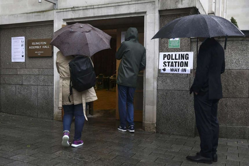 People queue in the rain outside a polling station for the UK referendum on the European Union in north London, on June 23, 2016.