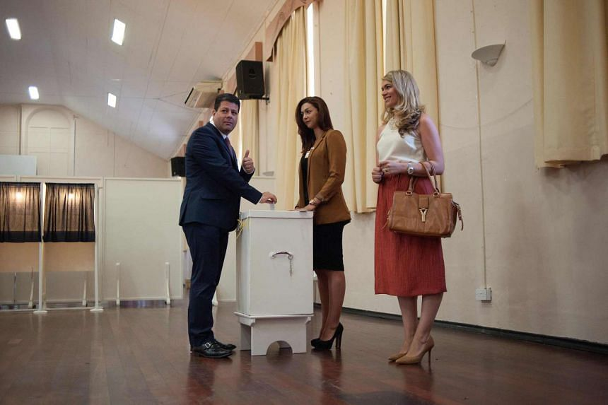 Chief Minister of Gibraltar Fabian Picardo (left) casts his ballot in the referendum on whether the United Kingdom should stay in or leave the European Union at their local polling station in Gibraltar on June 23, 2016.