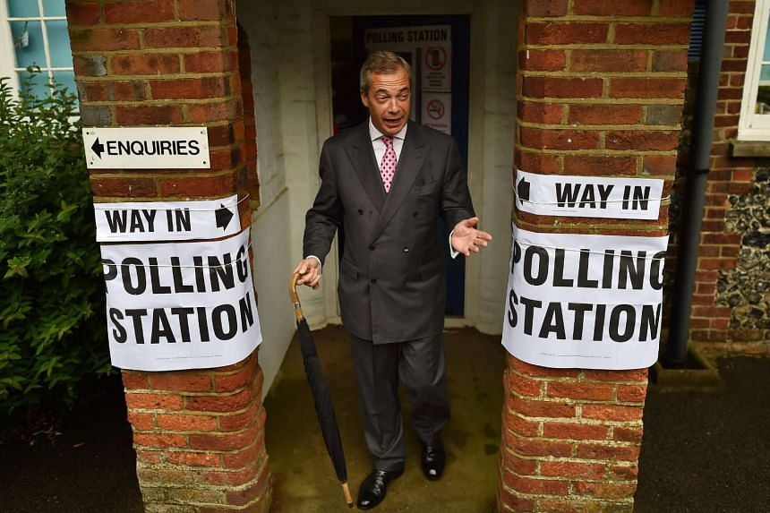 UK Independence Party leader Nigel Farage poses for photographers as he leaves a polling station south of London on June 23, 2016.