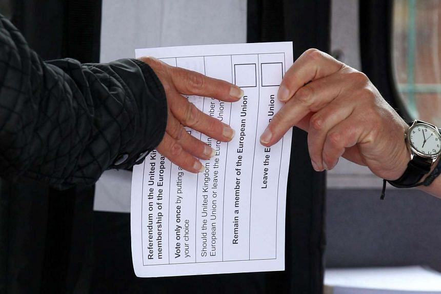 A volunteer hands an unmarked ballot paper to a voter inside a bus being used as a temporary polling station in Kingston-Upon-Hull, northern England, on June 23, 2016.