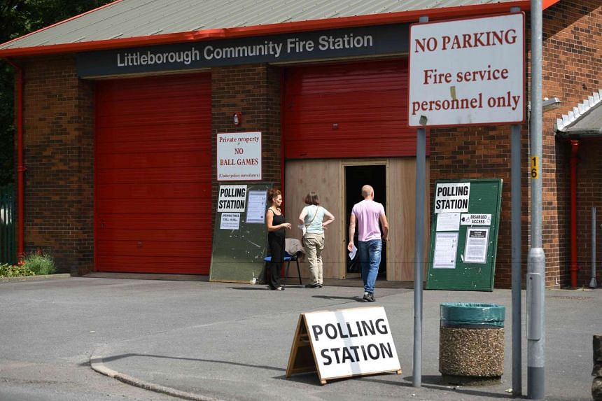 People arrive to cast their ballot papers inside a polling station set up at Littleborough Community Fire Station, near Rochdale, northern England, on June 23, 2016.