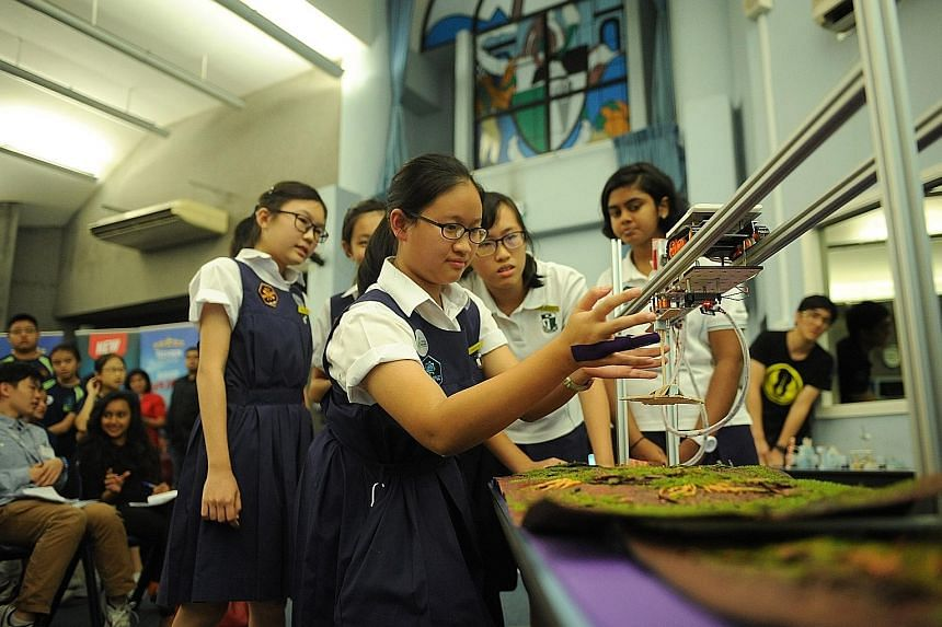Chang Li-Ann from Raffles Girls' School testing her team's prototype, the V-Wing Fighter, with her teammates looking on. They were among the 240 students involved in a competition under the Fuel Your School - Stem @ Central Singapore initiative held