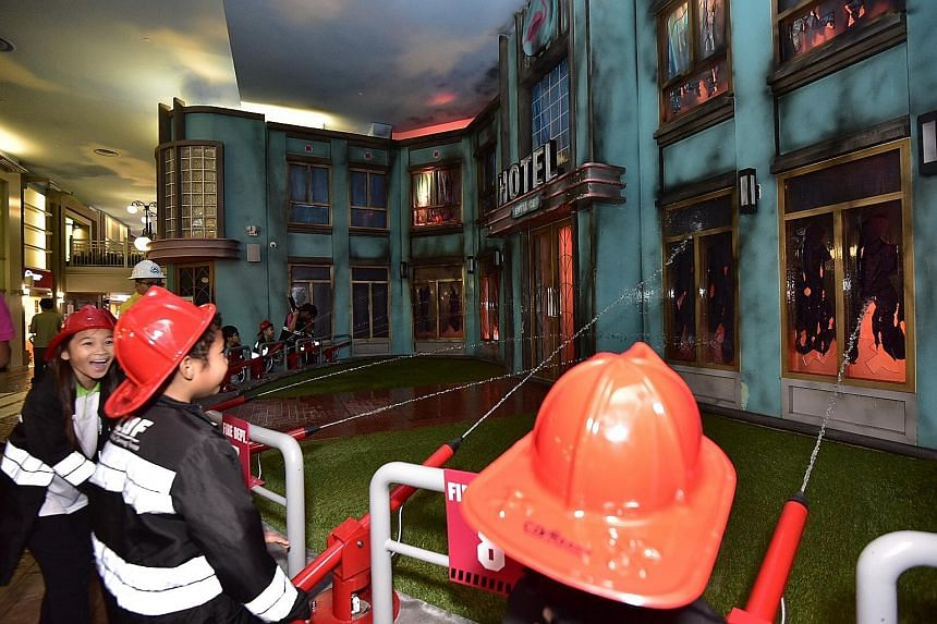 Children under Central Singapore District's Nurture 2.0 programme play-acting as firemen at KidZania yesterday. The volunteer scheme that helps kids with maths and English now includes non-academic activities with StarHub's support in the past six ye