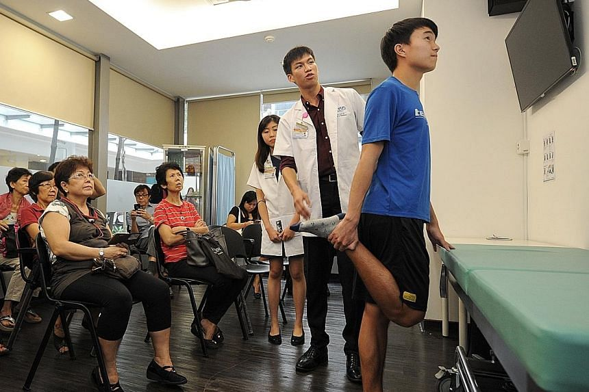 NUS Yong Loo Lin School of Medicine students (from right) Daryl Tham, Jonathan Leong and Goh Yue Shan share with their audience exercises that are suitable for those with osteoarthritis.
