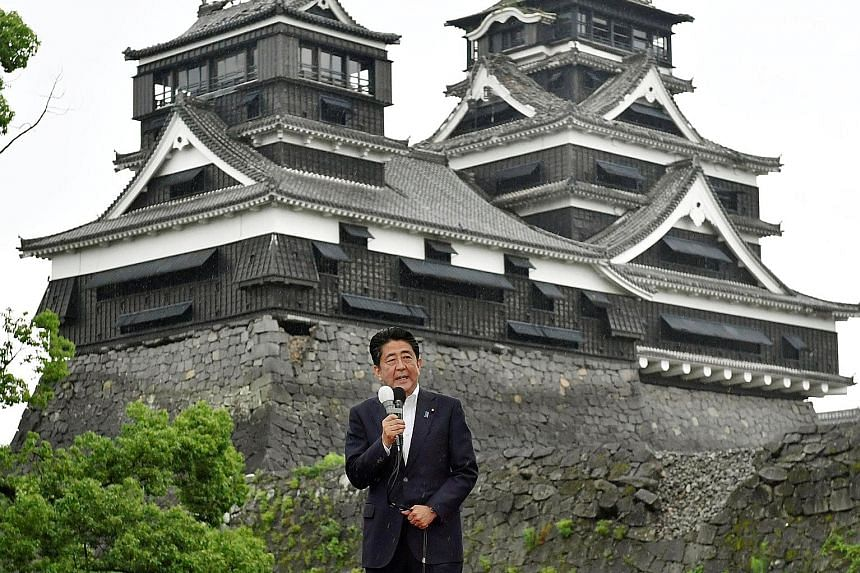 Campaign posters of candidates of the July 10 Upper House elections in Tokyo yesterday. Media surveys this week show that Mr Abe's ruling bloc will likely win the polls. Mr Abe speaking with the quake-damaged Kumamoto Castle in the background as camp