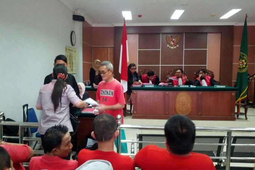 Singaporean Teo Boon Tiak (in red) went on trial today (June 23), after being accused of using forged documents to obtain an Indonesian passport.