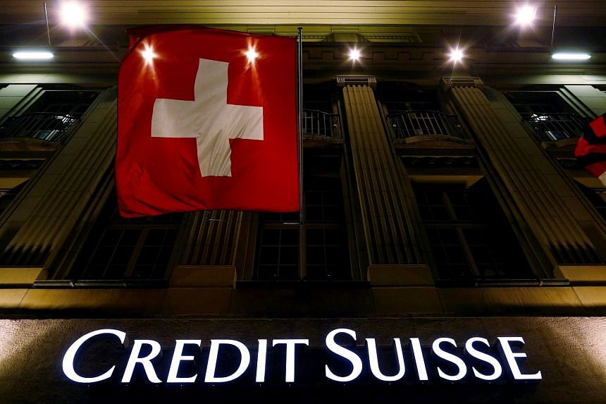 The logo of Swiss bank Credit Suisse is seen below the Swiss national flag at a building in the Federal Square in Bern, Switzerland.