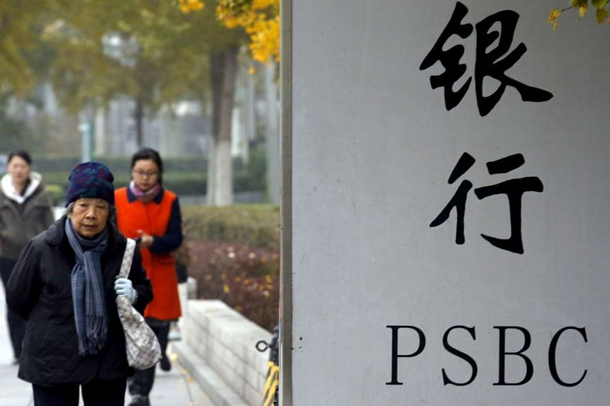People walk past a sign outside a branch of Postal Savings Bank of China (PSBC) in downtown Beijing, on Nov 12, 2015.