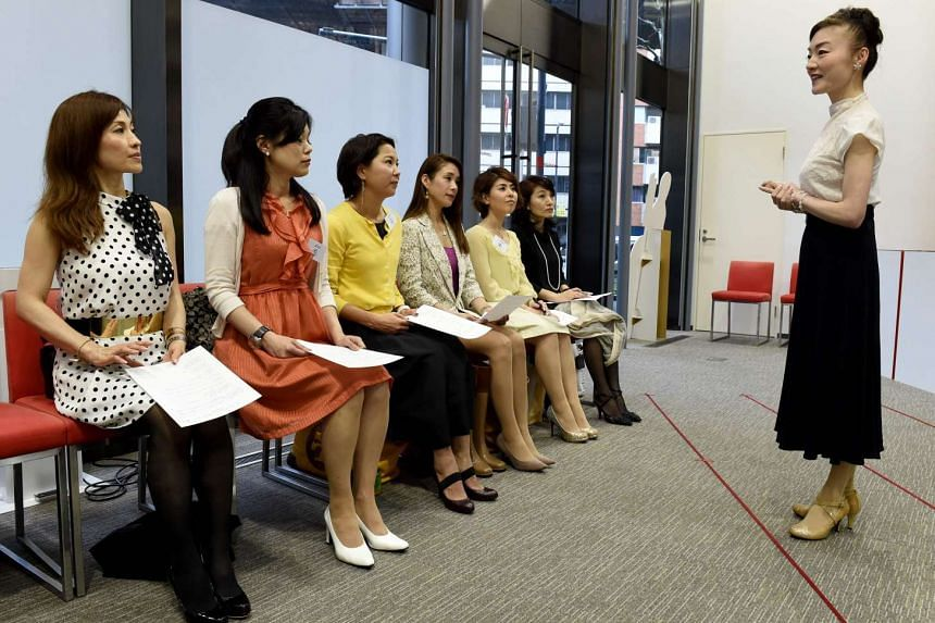 "The Japan High Heel Association managing director ""Madame"" Yumiko (right) giving a lesson on high heels in Tokyo on April 7, 2016."