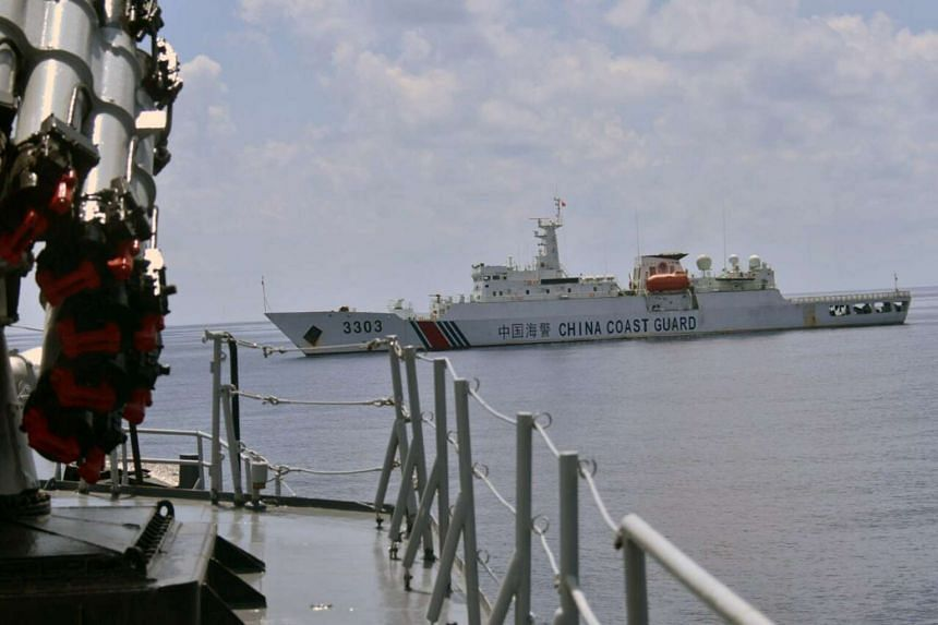 A Chinese Coast Guard vessel passes near the Indonesian Navy vessel KRI Imam Bonjol when it was attempting to detain the fishing boat Han Tan Cou near Natuna Islands, on June 17, 2016.