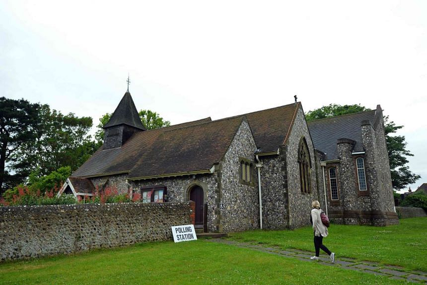 A woman arrives to cast her vote at the Parish church of St. Peter in West Blatchington, near Brighton in southern England, on June 23, 2016.