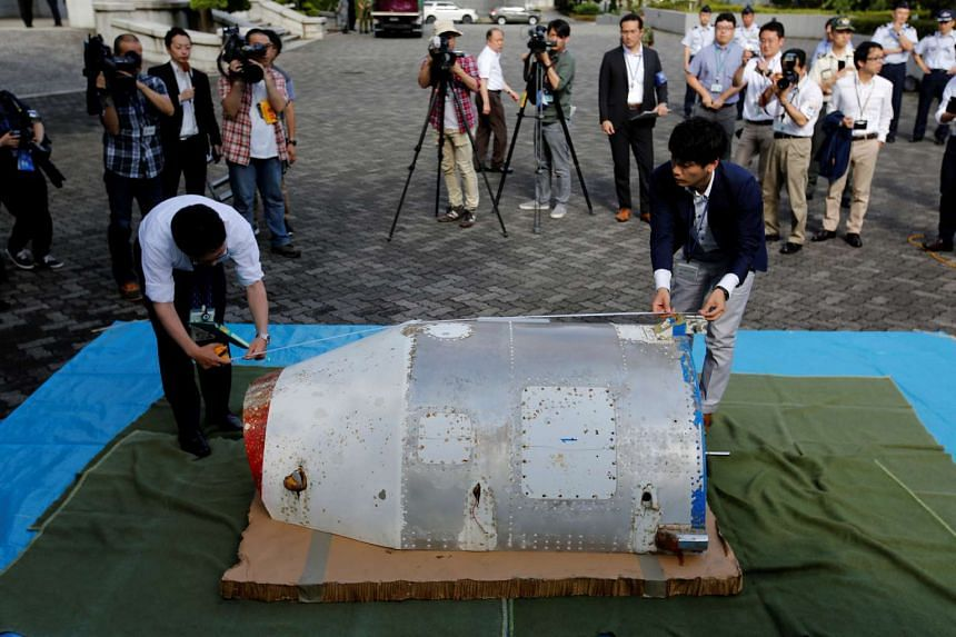Officials of Japan's Defence Ministry check an object, suspected to be half of a nose cone from a North Korean rocket launched in February, in Tokyo, on June 23, 2016.