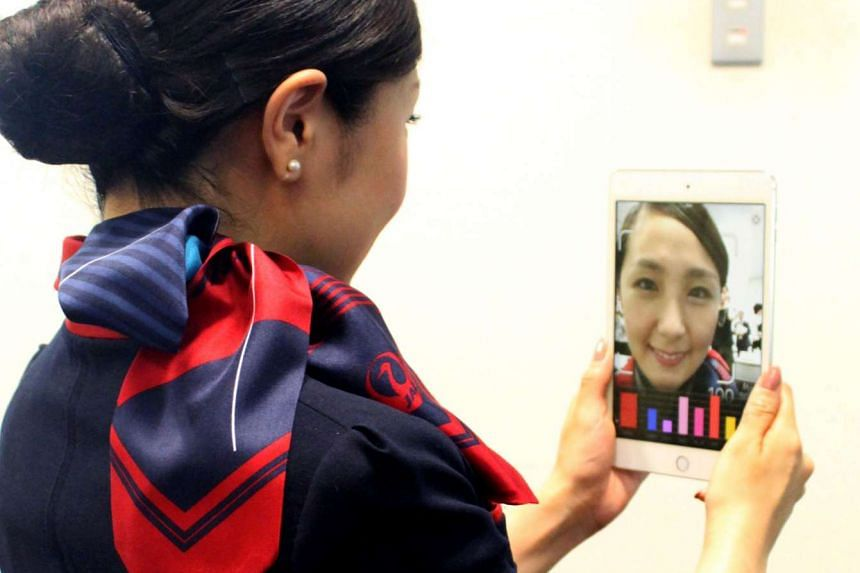 A Japan Airlines flight attendant checking her smile using a tablet device installed with a Shiseido app in Tokyo, in an undated picture by Japan Airlines on June 23, 2016.