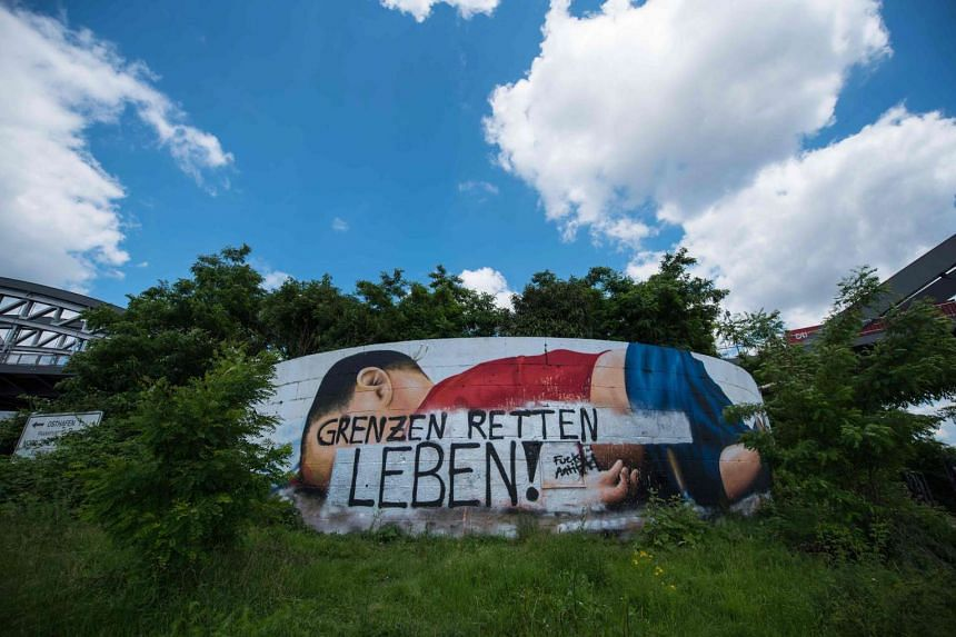 "The message ""Borders save lives"" is written on the colour painting of the three-year-old Aylan Kurdi in Frankfurt, western Germany on June 22, 2016."