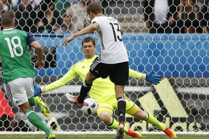 Germany's Thomas Muller failing to score past Northern Ireland goalkeeper Michael McGovern. Both sides reach the last 16 after the Germans' 1-0 win.