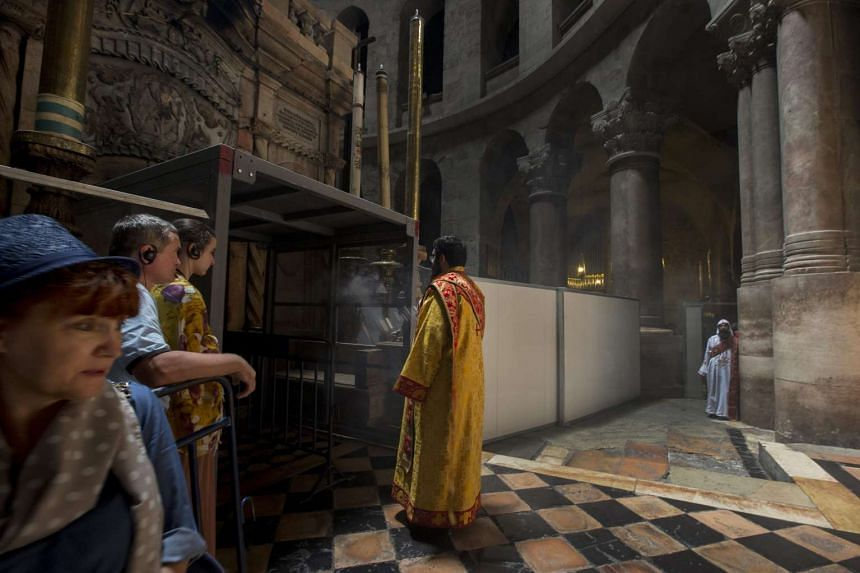 A Christian Orthodox clergy swings incense as he sanctifies area at the entrance to the Tomb of Jesus Christ (left).