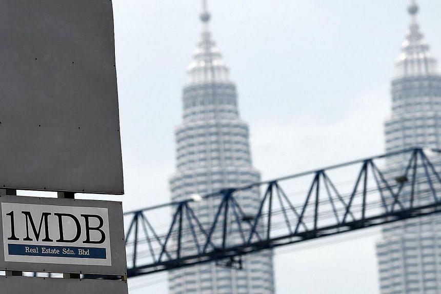 A 1MDB billboard with Malaysia's iconic Petronas Towers in the background in Kuala Lumpur.